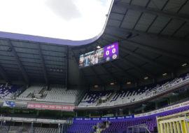 Een foto van de opbouw van een 40m² ledscherm in het Lotto Park van RSC Anderlecht. Het scherm hangt vast aan de bovenkant en het beeld wordt getest